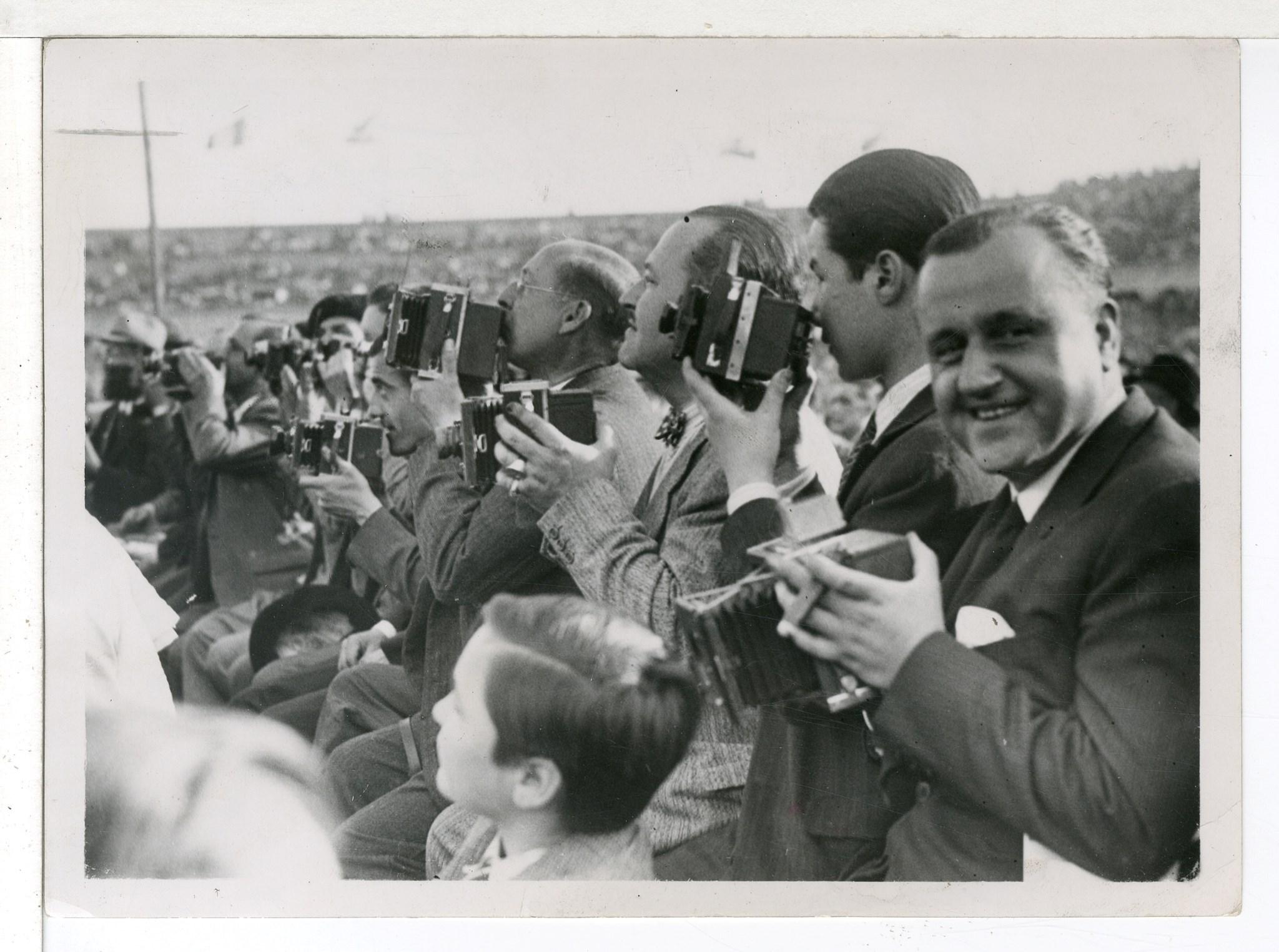 <p>Josep Gaspar, Josep Brangulí i Carlos Pérez de Rozas, entre d'altres fotògrafs, cobrint el combat de boxa Uzcudun-Carnera a Montjuïc, l'any 1930. Foto: Pablo Luís Torrents</p>